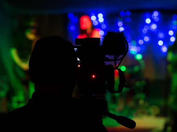 A camera in silhouette with performers in background